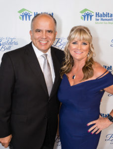 Raul Salinas with Habitat LA President and CEO Erin Rank smiling for a photo in front of a step and repeat.