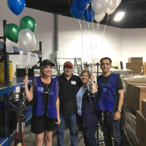 Four ReStore volunteers standing inside a ReStore holding baloons