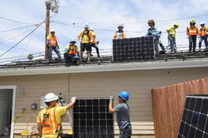 Multiple Southern California Edison volunteers standing on a roof with safety gear on while holding a solar panel. Two more volunteers on the ground holding another solar panel.