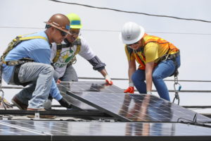 Three Southern California Edison volunteers installing solar panels on a roof.