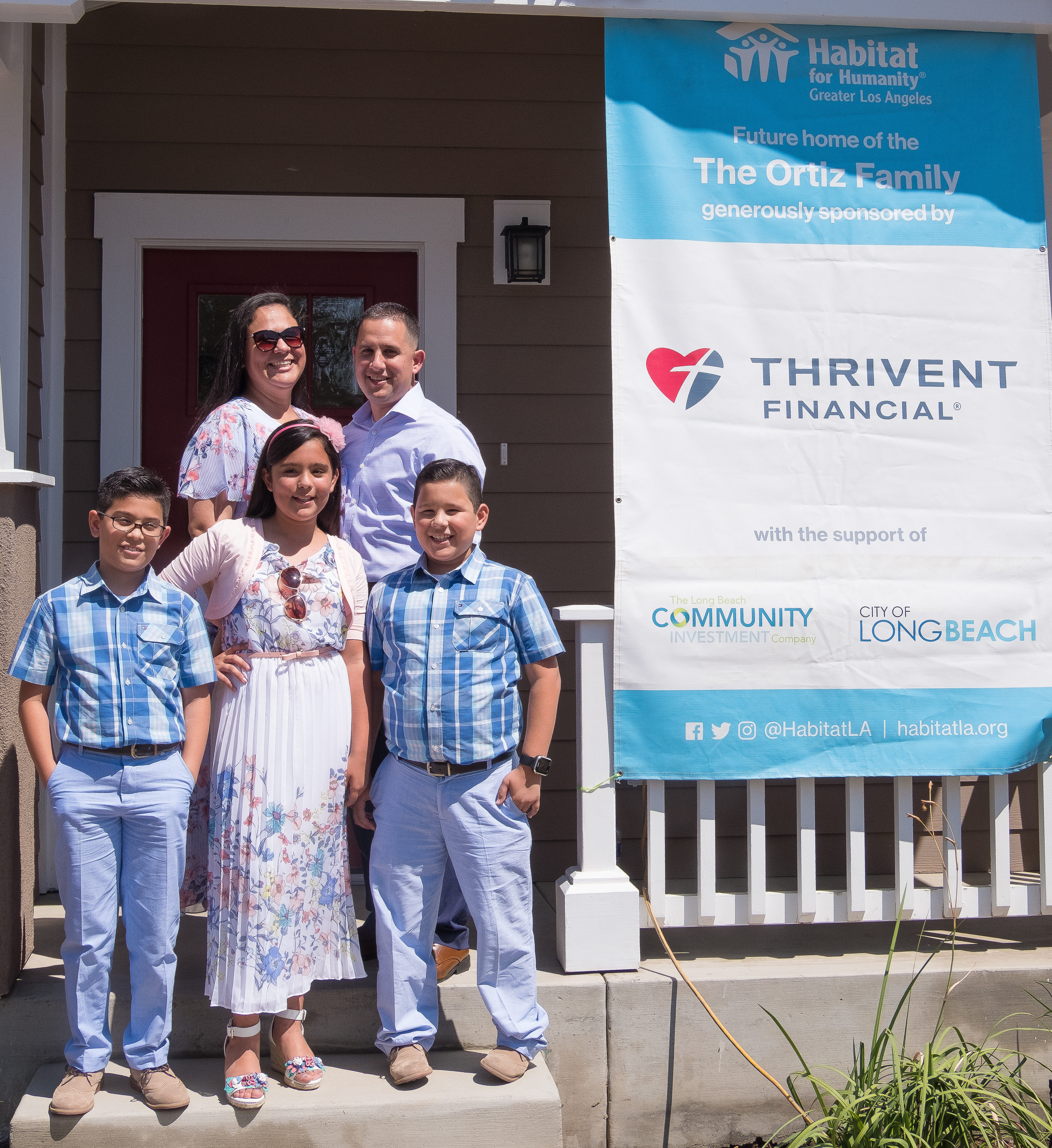The Ortiz family standing in front of their brand new home at their home dedication.