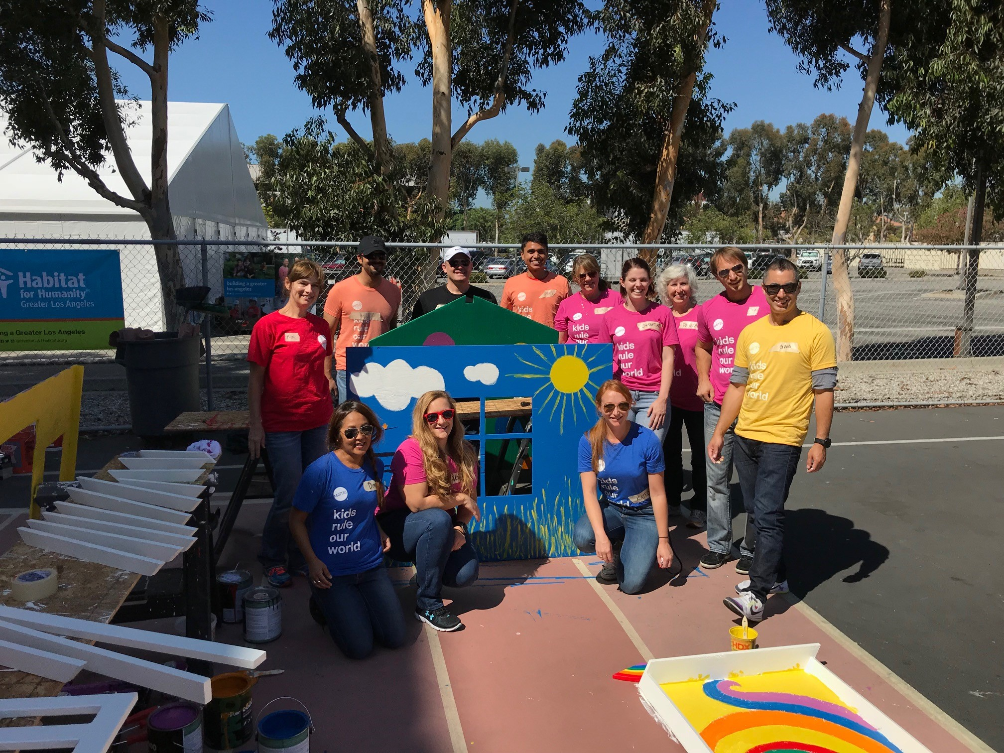 Mattel volunteers standing in front of their playhouse they painted for a group photo.