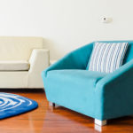 A photo of half of a couch, a blue rug, and a blue chair.