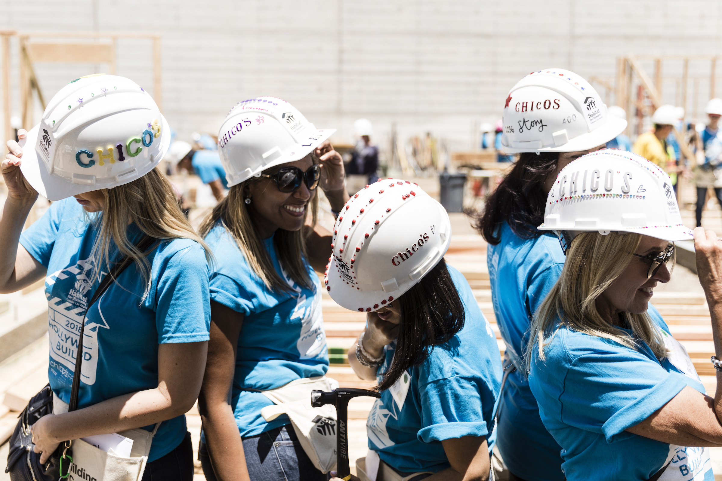 Volunteers at Power Women, Power Tools 2018 showing off their newly decorated hard hats on the construction site.