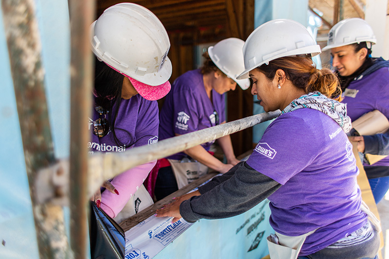 Four Lowe's Heroes volunteers installing window frames on a construction site.