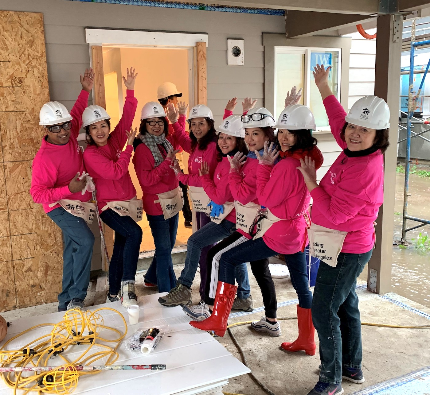 Jeunesse Kids distributors smiling on a construction site as they point to the wall they just worked on.