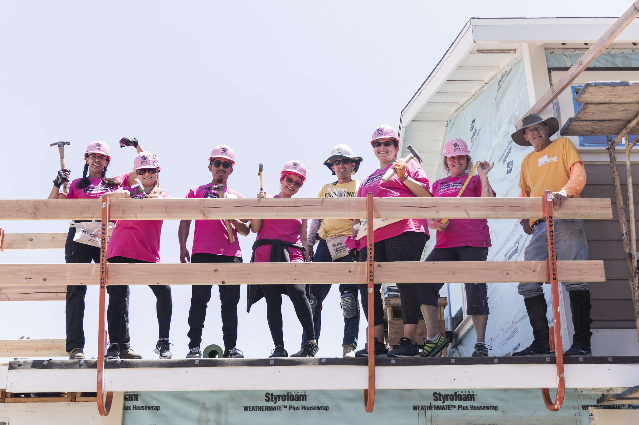 A group of volunteers standing on a roof behind a safety railing, smiling and holding hammers as they pose for a group photo.