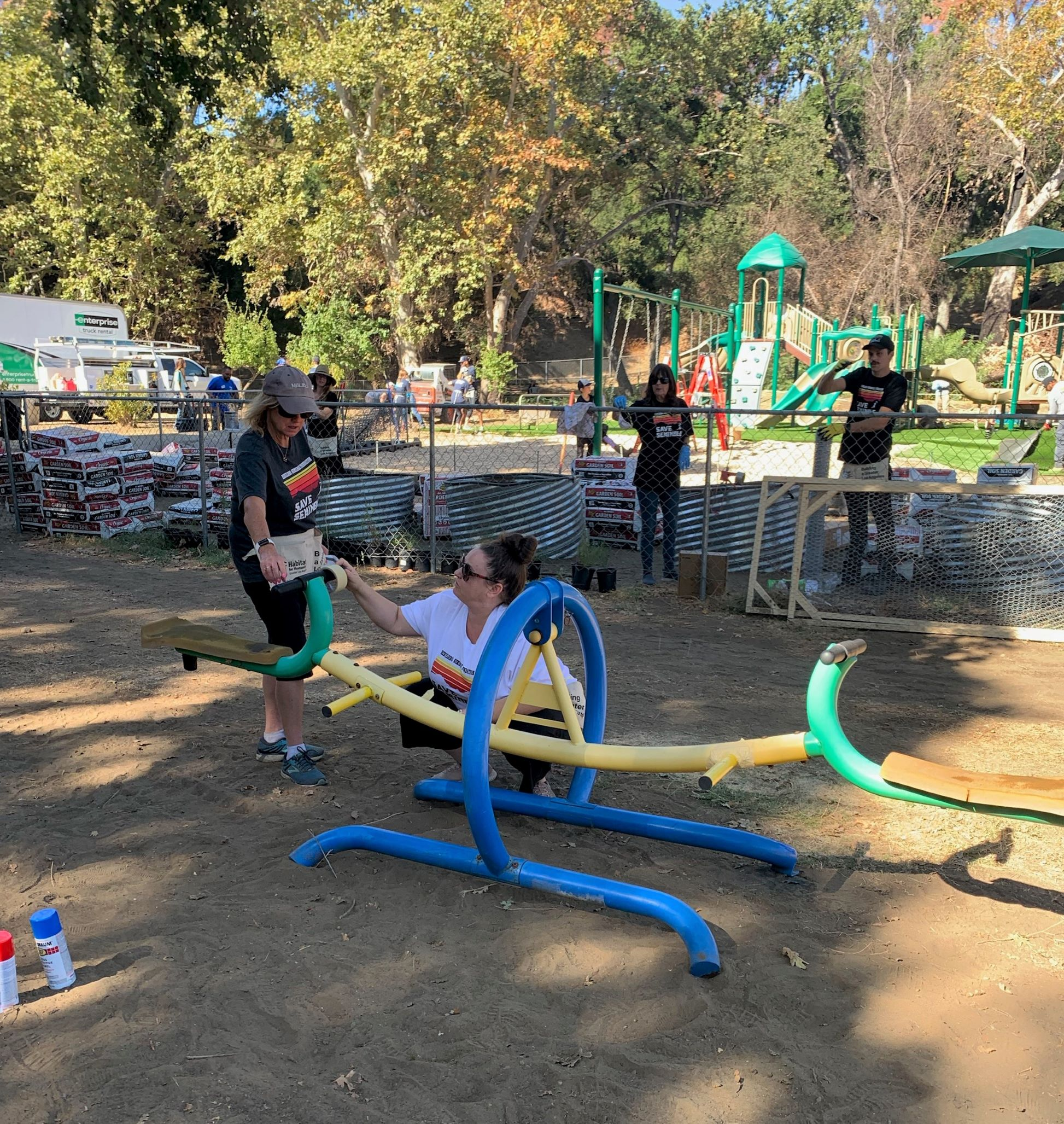 Two volunteers working on a teeter totter at a playground that is under construction.