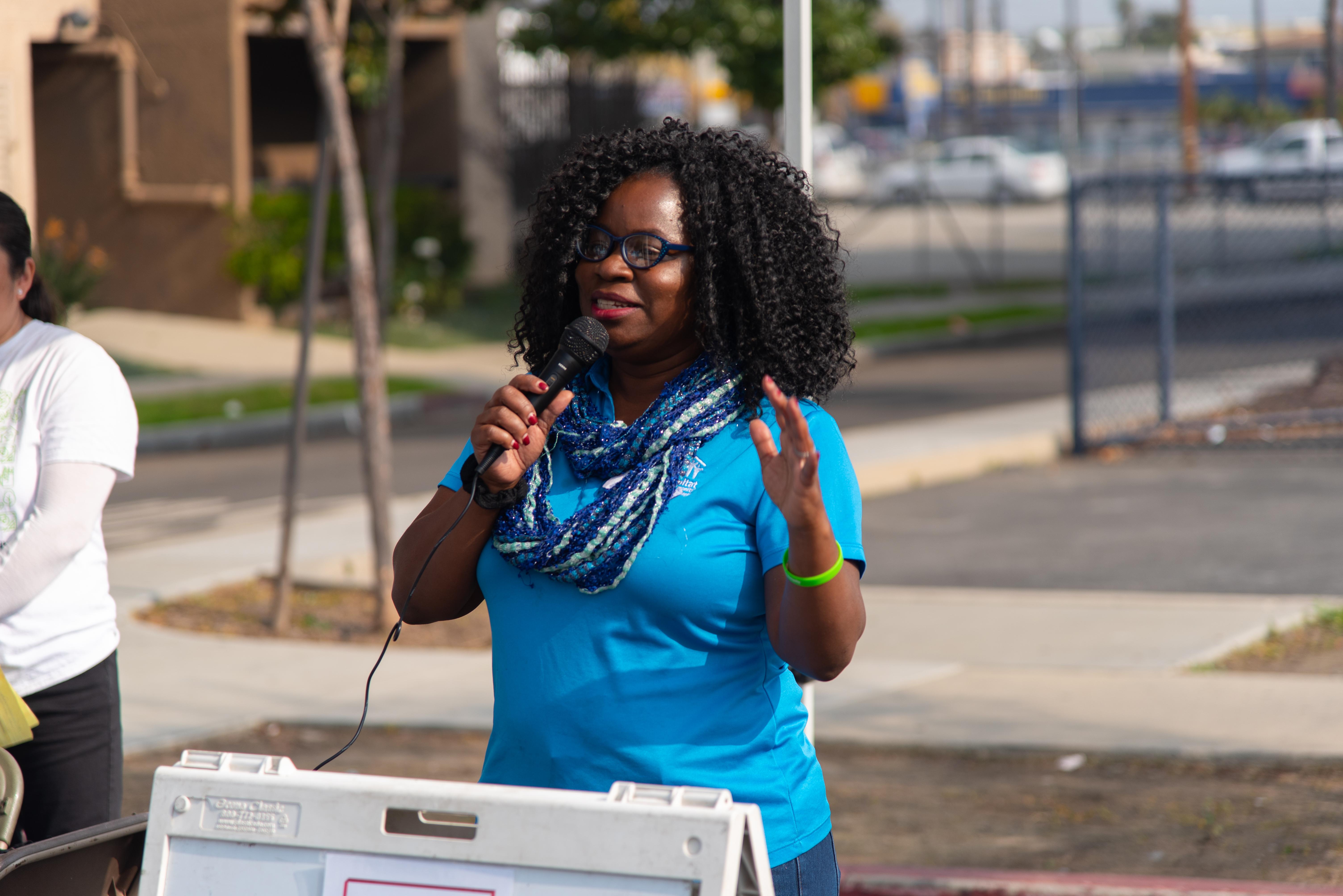Habitat LA employee talking into a microphone to a group of people in the Washington Neighborhood.