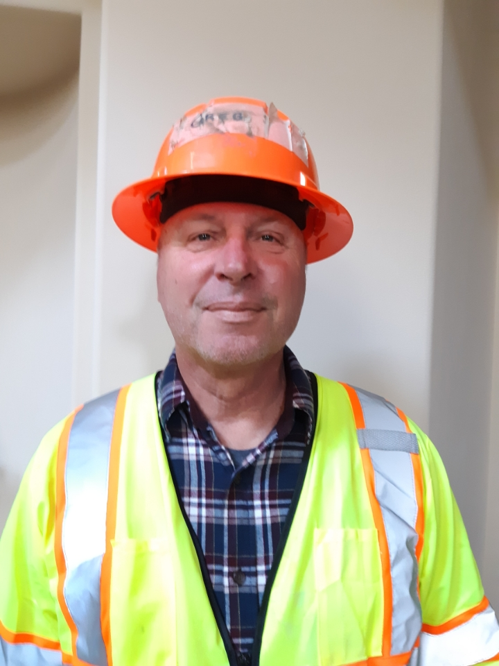 Greg Raasch smiling with construction gear on.