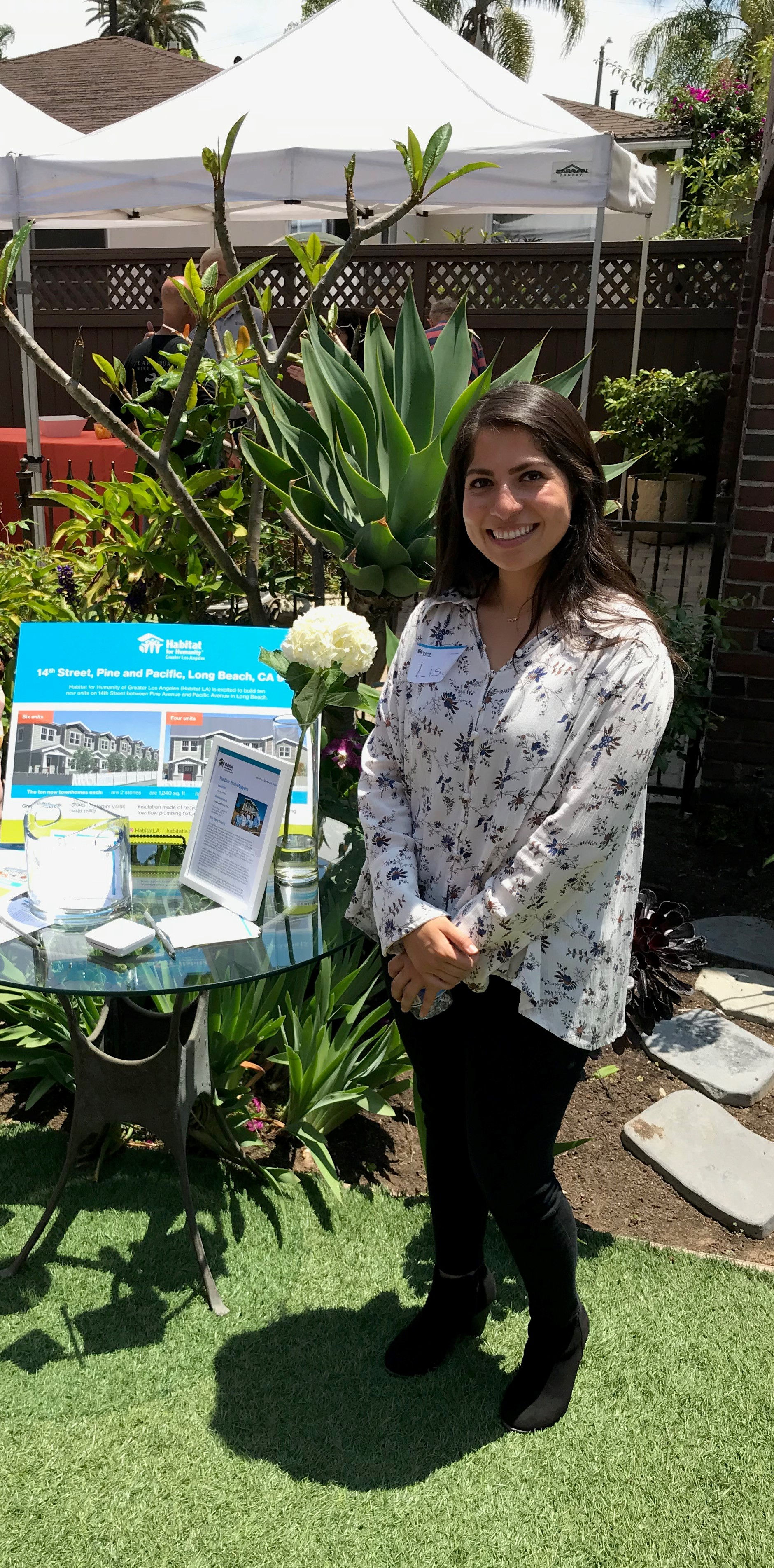 Lisa Homeidan smiling in front of a Habitat LA display table.