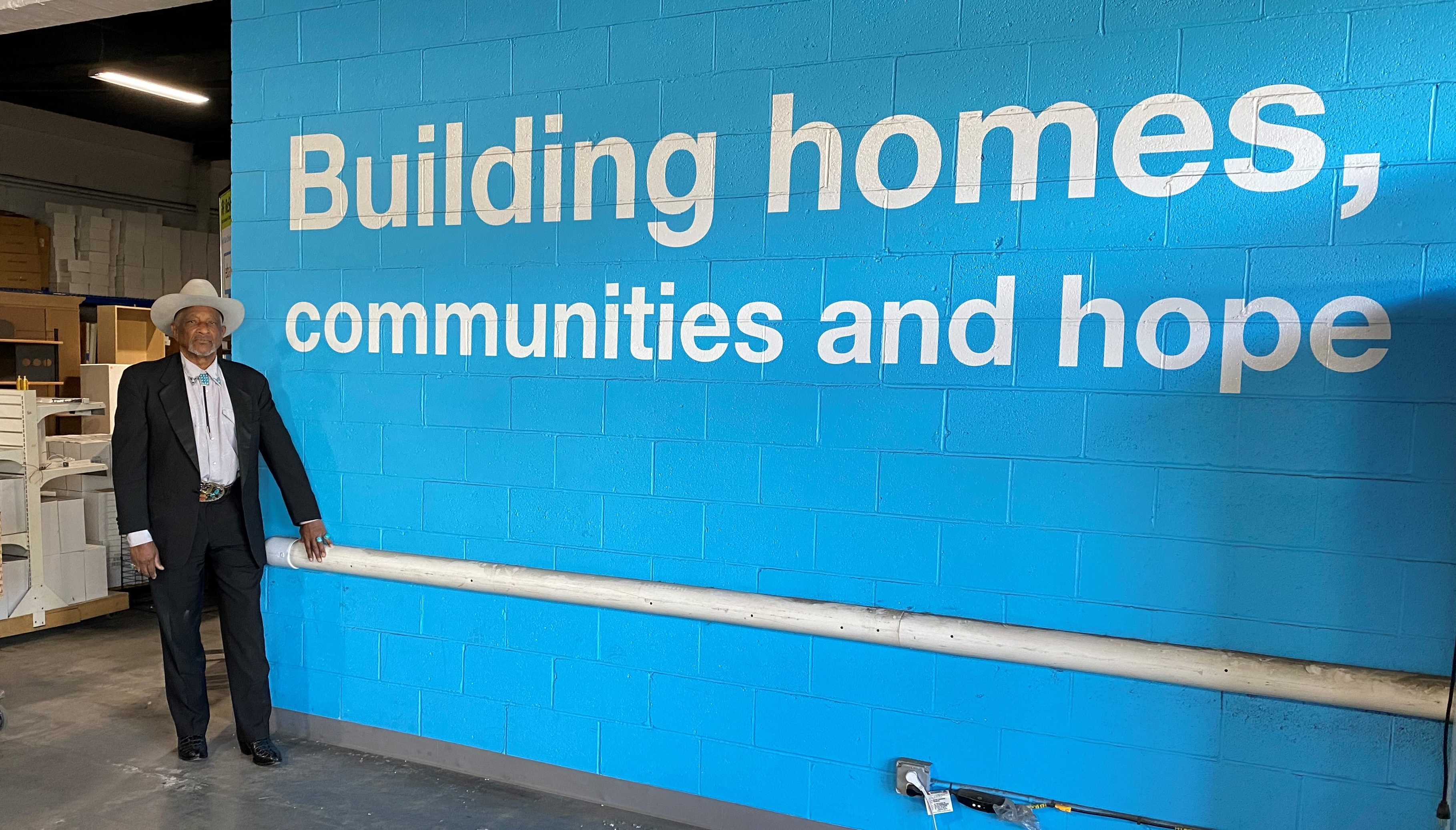"""Al Lynch smiling in front of a wall that says """"Building homes, communities and hope""""."""