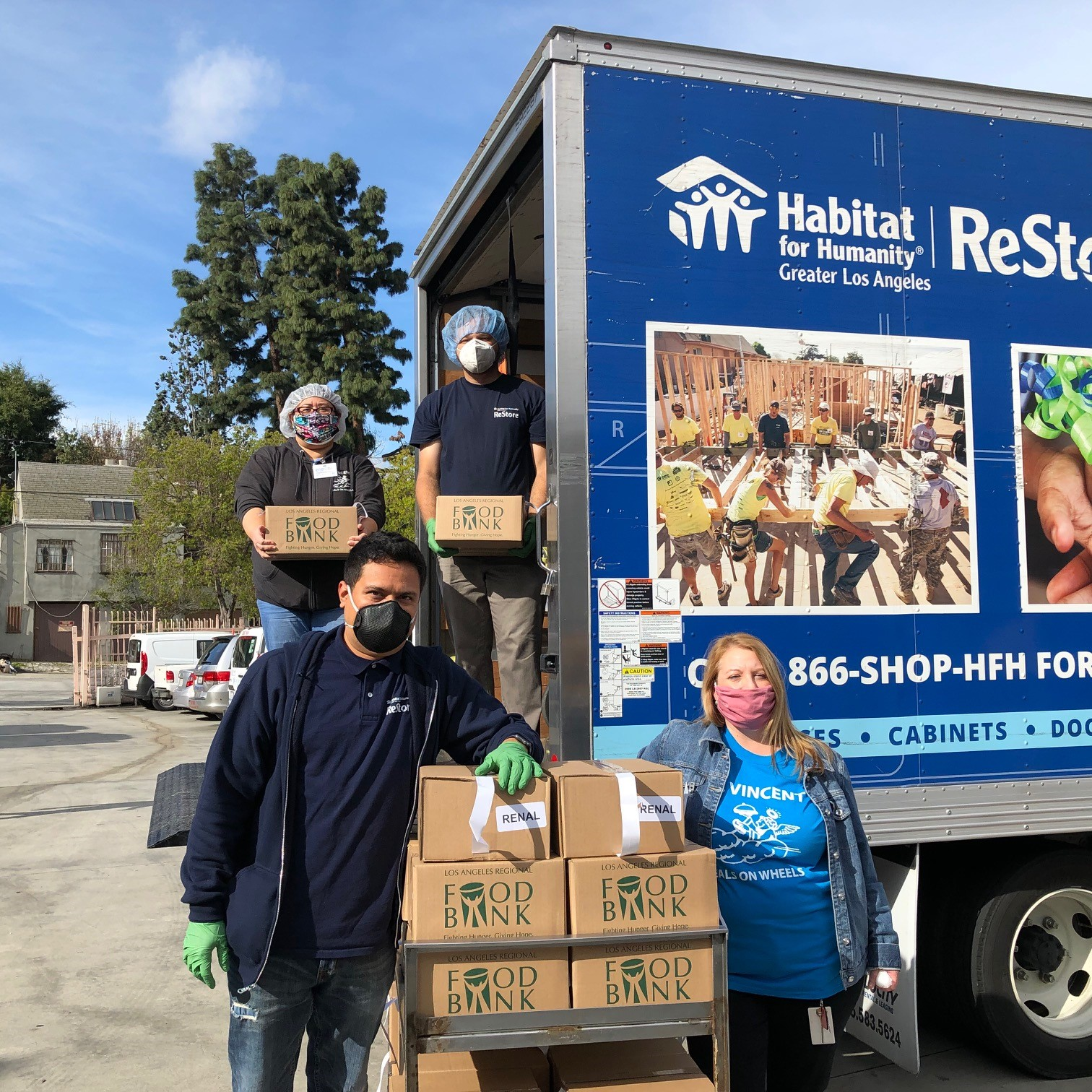 ReStore employees and Meals on Wheels employee standing on the back of a ReStore truck pausing from unloaded food to pose for a photo.