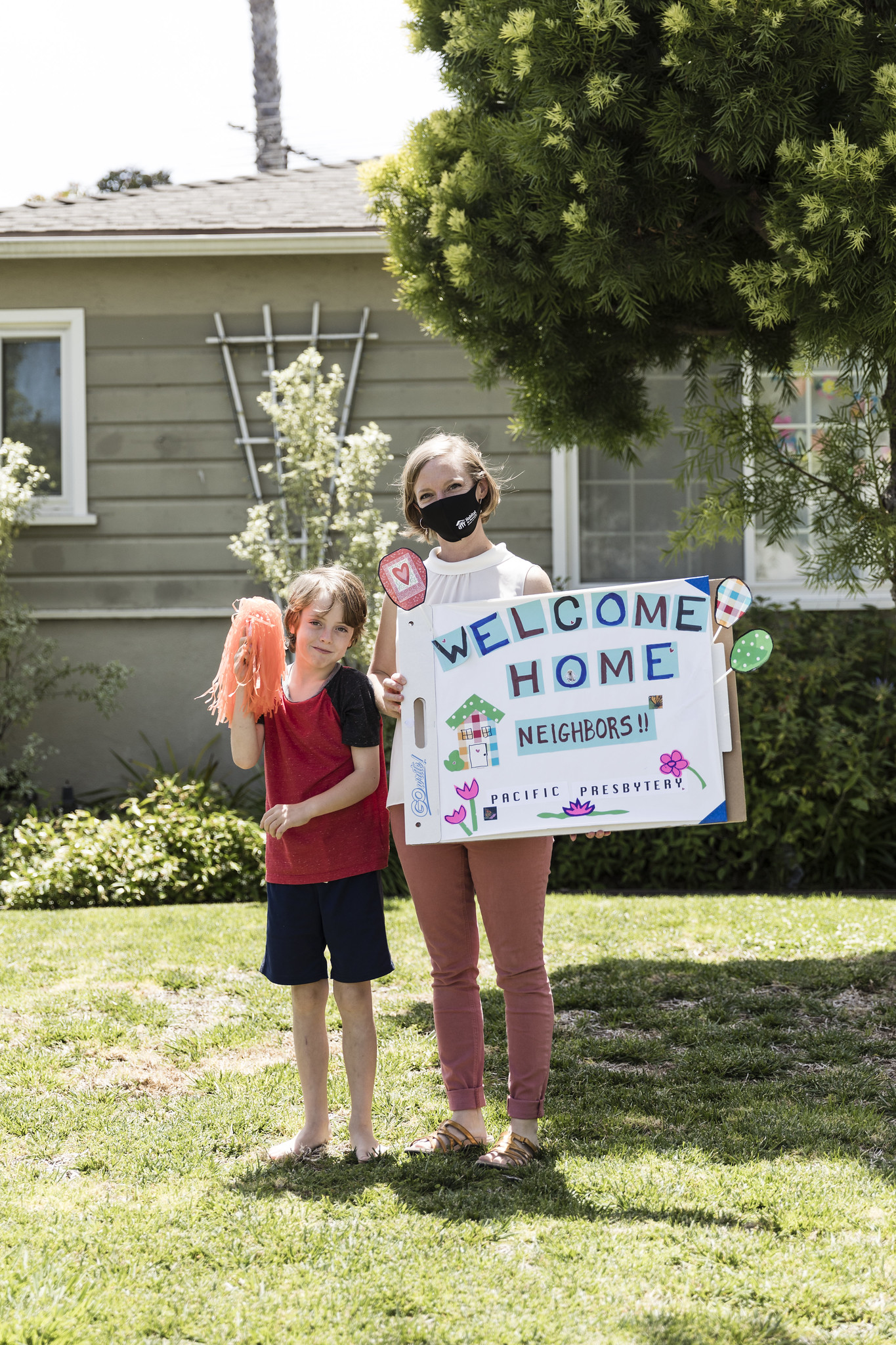 "Mom and child standing in their front yard holding ""welcome home"" sign and a pom pom."