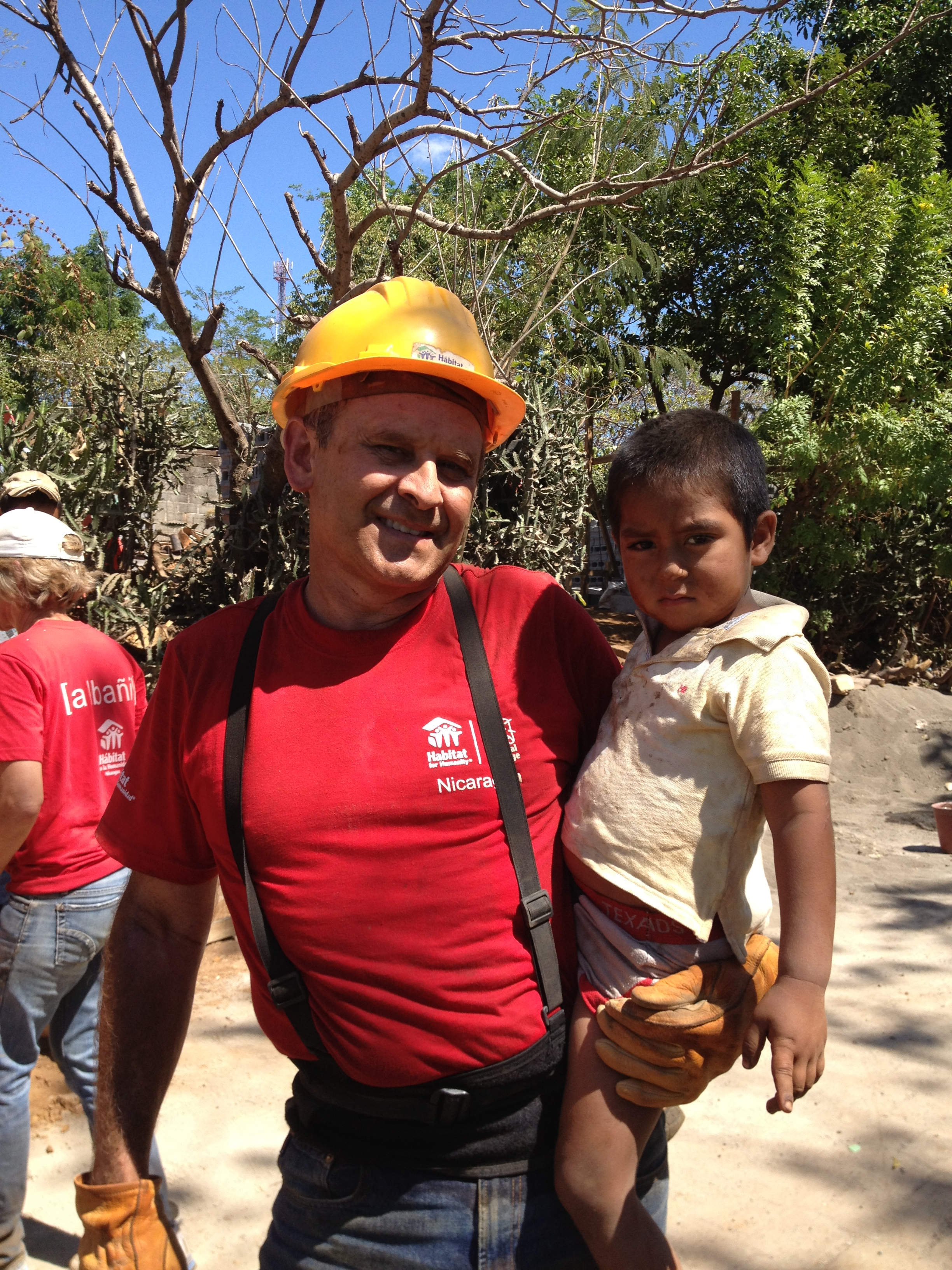 A man standing and smiling with a hard hat on while holding a toddler for a photo.
