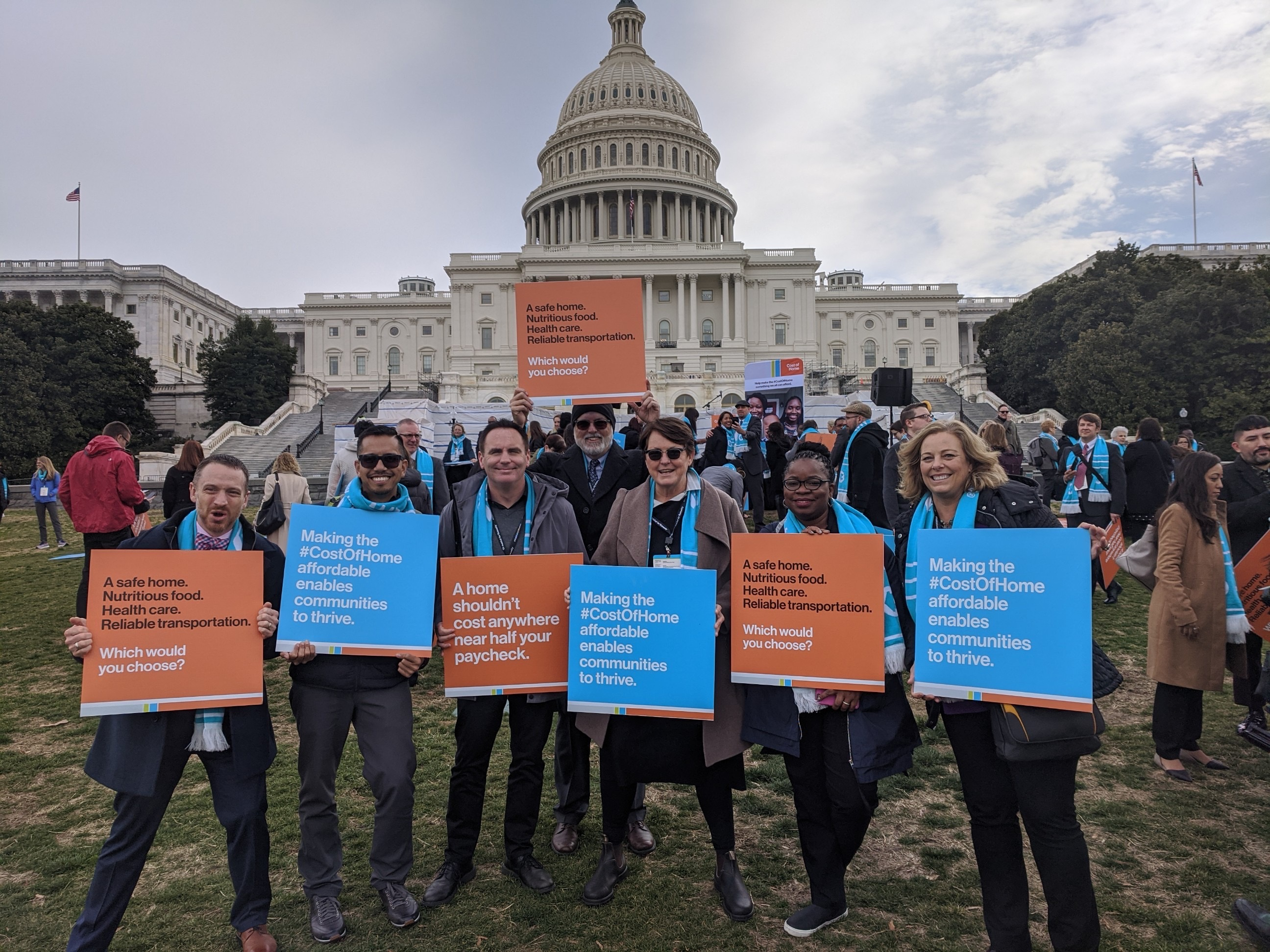 The California Delegation standing and smiling for a group photo while holding signs in front of the Capitol Building.