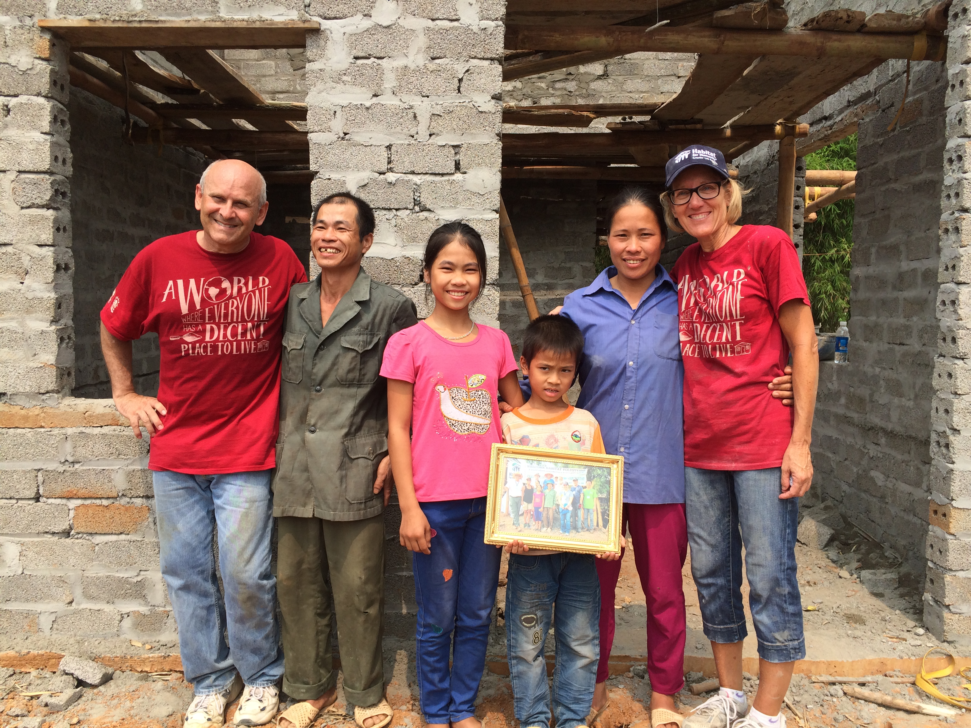 Former Board member, his wife, and a family they built with in Vietnam standing and smiling for a photo.