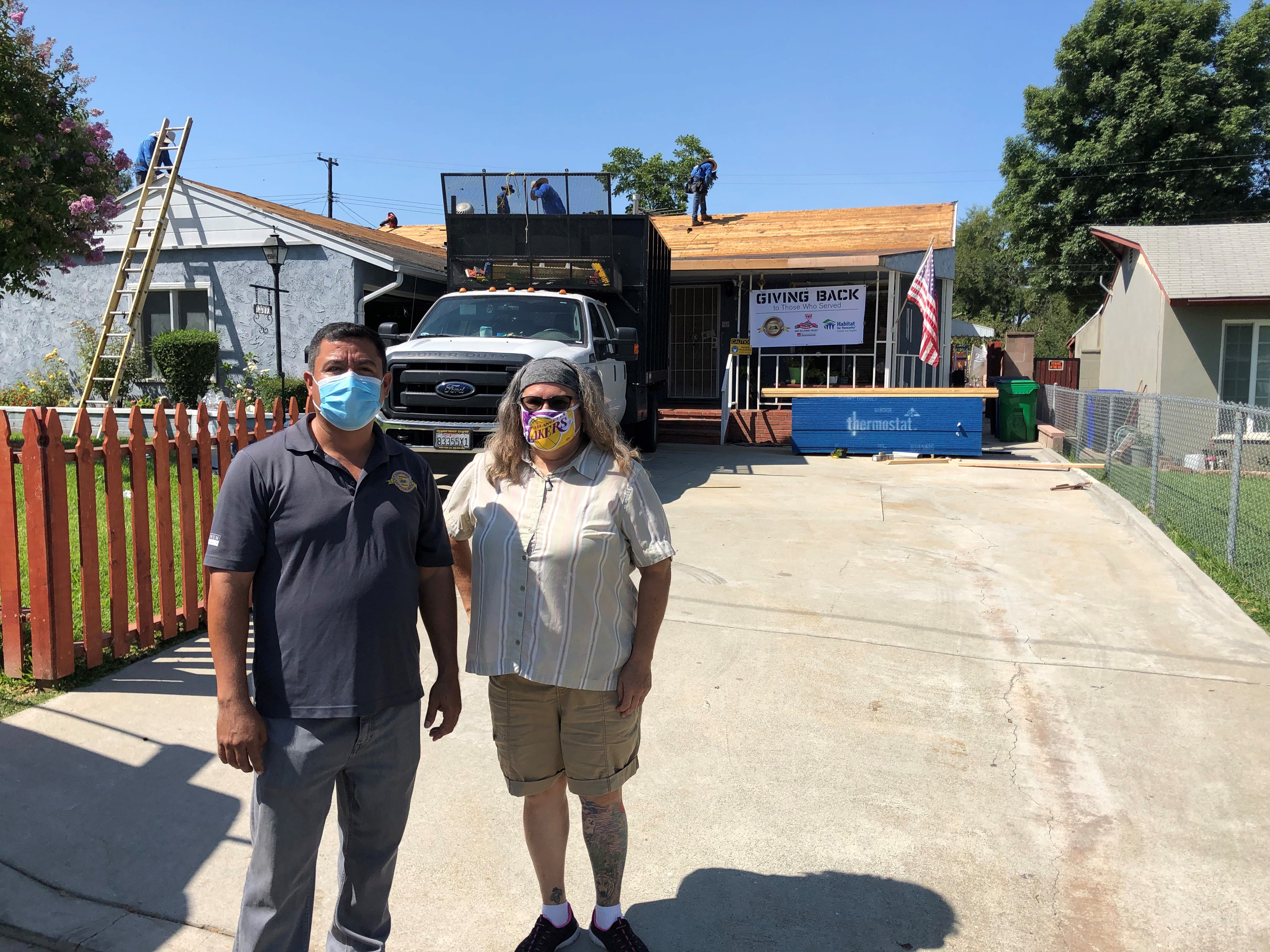 Two people standing in front of a new roof going on a house.