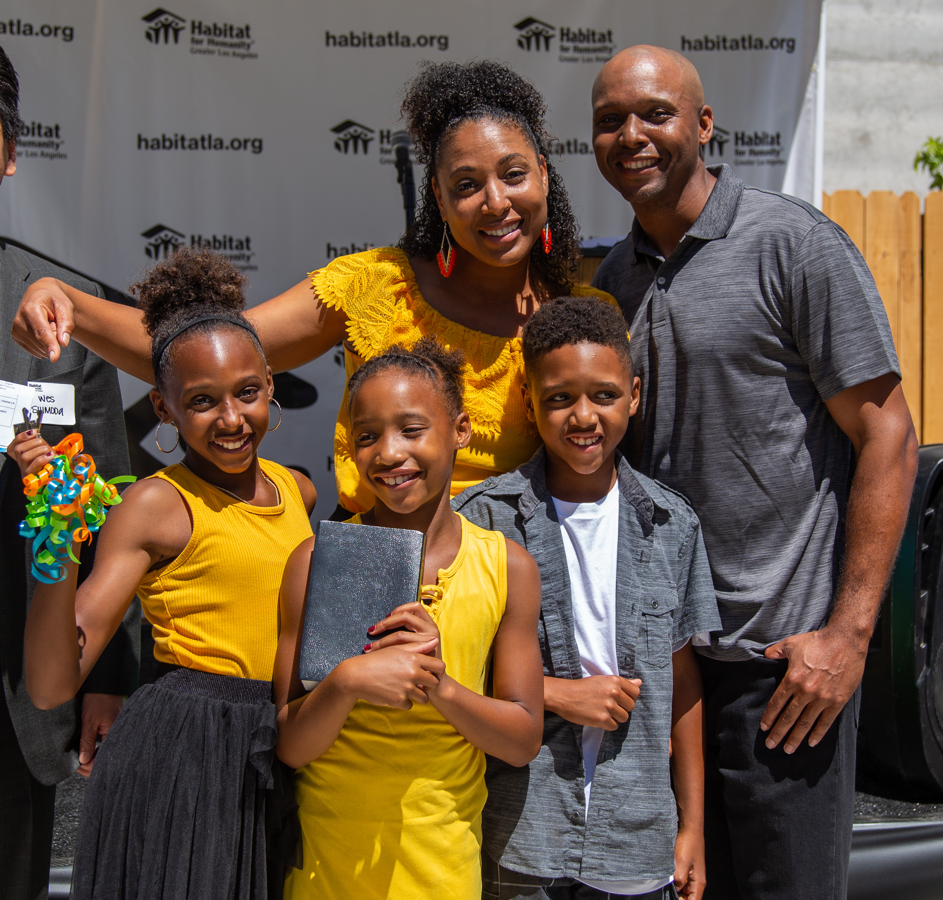a family smiling for a group photo holding keys to their new home and a bible.