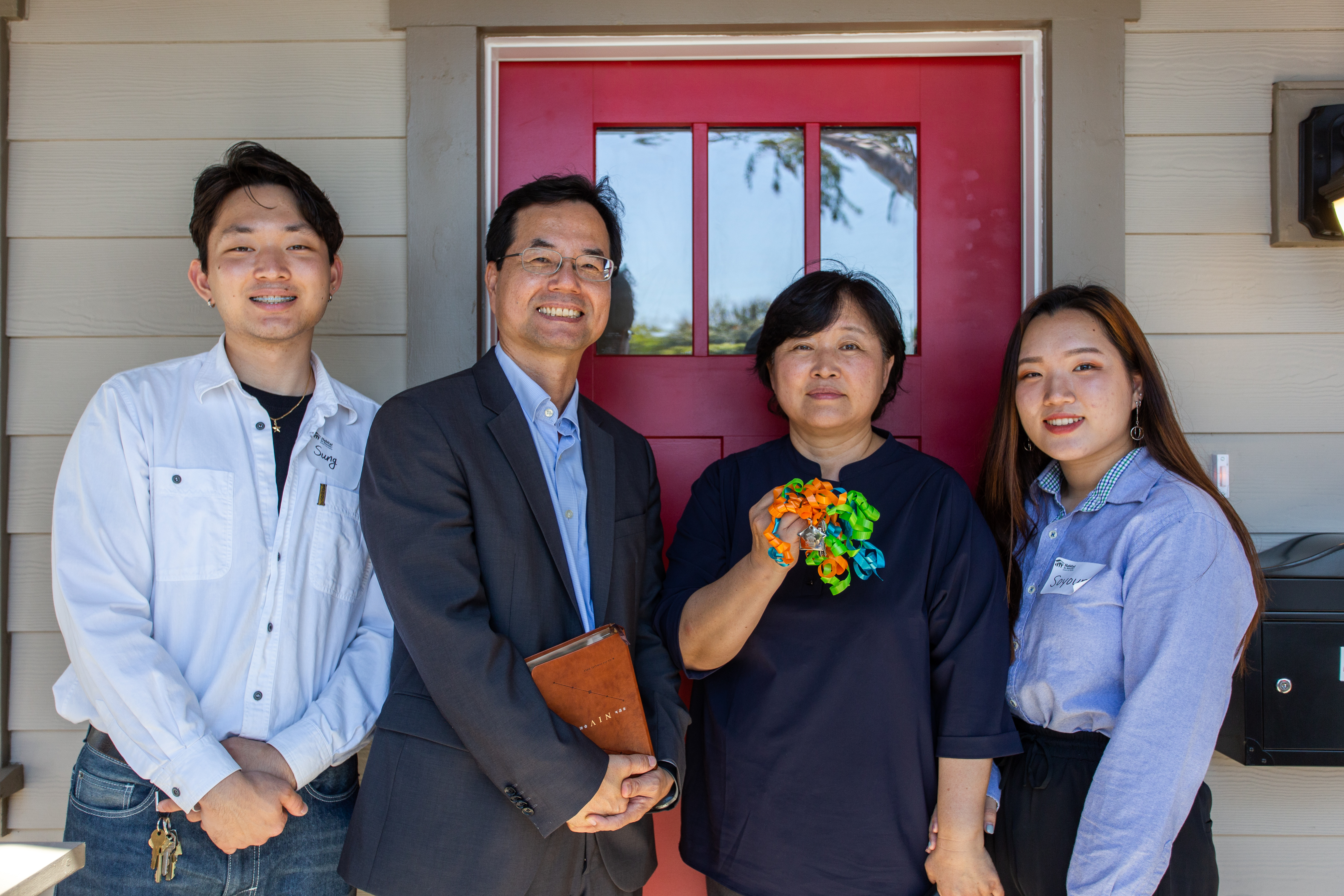 A family of four standing in front of a red door holding keys and smiling.